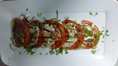 Ensalada de tomate con queso de cabra rúcula y frutos secos aderezada con reduccion de vinagre de jerez
